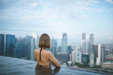 SINGAPORE - JAN 19, 2016: back view of woman in water pool on roof looking at city stock vector