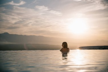 Young woman relaxing in beautiful pool at sunset, pamukkale, turkey stock vector