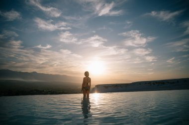 Back view of young woman standing in beautiful natural pool and looking at majestic landscape in pamukkale, turkey stock vector