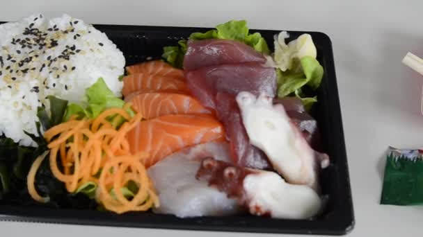 Sashimi with bluefin tuna, salmon, amberjack, octopus. As a vegetable plant seaweed, salad, carrot, ginger. Seasoning wasabi, soy sauce. Full hd video.