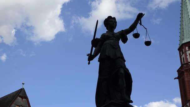 Frankfurt, Németország - 2019. augusztus: A Rmerberg teret az igazság forrása jellemzi. A szobor tartja a szimbolikus lemezek a skála, enyhén mozgott a szél, mint a felhők.