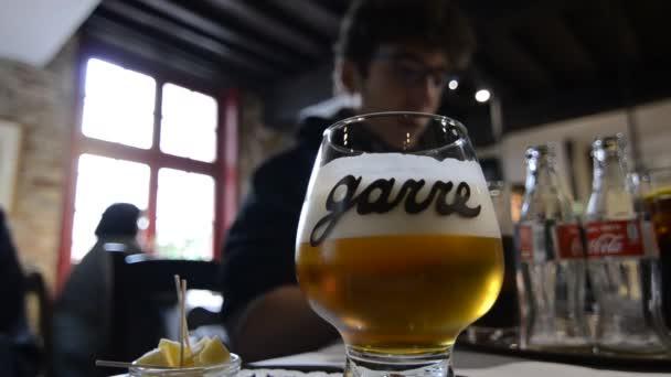 Bruggy, Belgie - srpen 2019: V historickém a okouzlujícím pivovaru La Garre ochutnávka piva. Dva chlapci čekají na obsílku, v pozadí má pár hrníčků na stole.