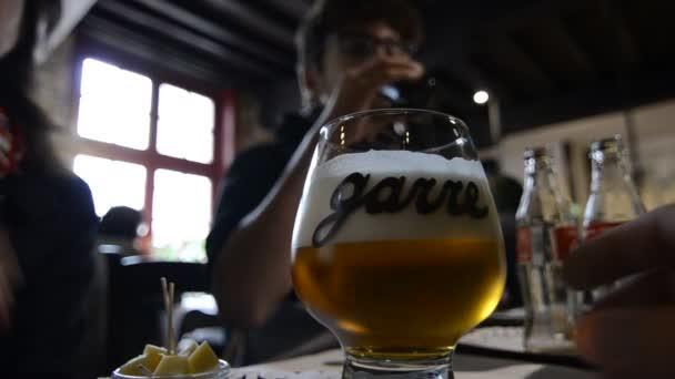 Bruges, Belgium - 2019. augusztus: A történelmi és bájos La Garre sörfőzdében, sörkóstolón. Két fiú várja a tálalást, a háttérben egy pár bögréi vannak az asztalon..
