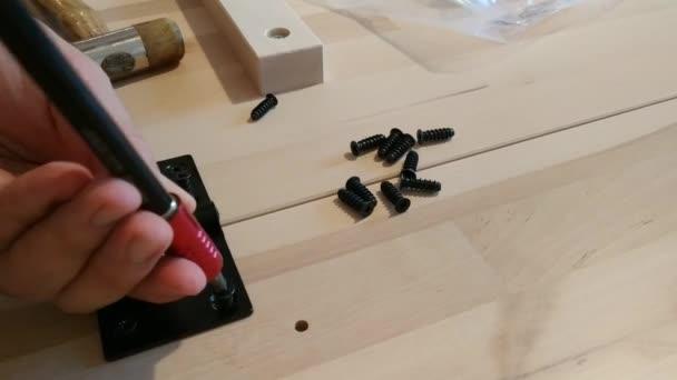 Befestigung mit einem schwarzen Metallscharnier auf zwei hellen Holzbrettern. Der Schraubenzieher wird zum Schrauben verwendet.