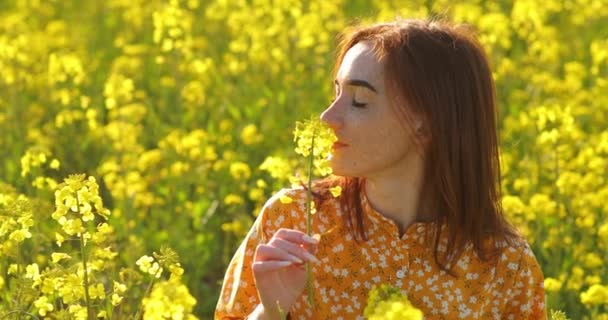 Young redhead woman enjoying nature and sunlight in canola field. redheaded young woman with freckles. Happy young woman of wildflowers in yellow field in sunset lights, summer time.