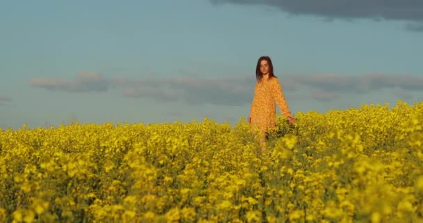 Beautiful woman in yellow dress walk through a yellow field with canola flowers. Young beautiful girl in a red dress close up in the middle of the yellow field with the radish flowers closeup.