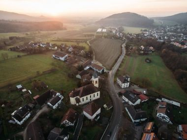 Aerial view of houses, church and green fields at foggy sunrise, Germany stock vector