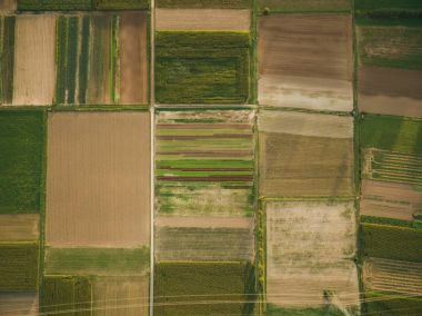 aerial view of green agricultural fields with power line, europe