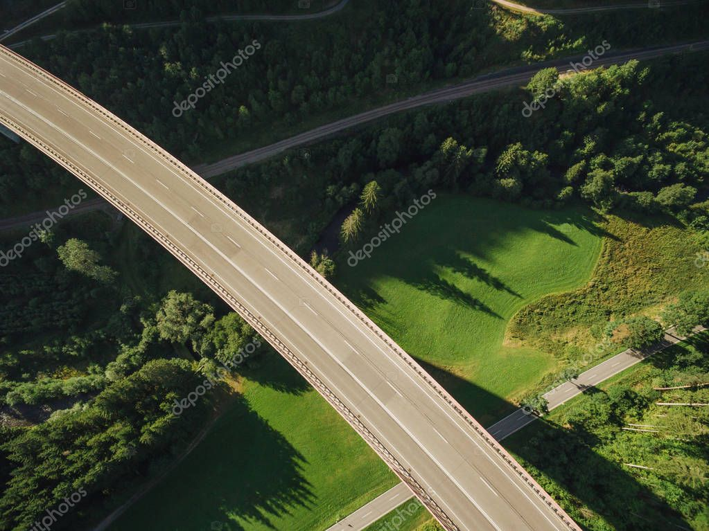 aerial view of empty bridge over beautiful green forest
