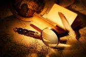 zvětšovací sklo s knihou, pera a svět mapa na staré mapy
