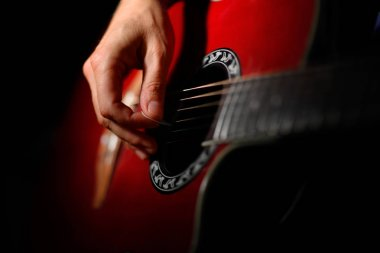 playing the red acoustic guitar