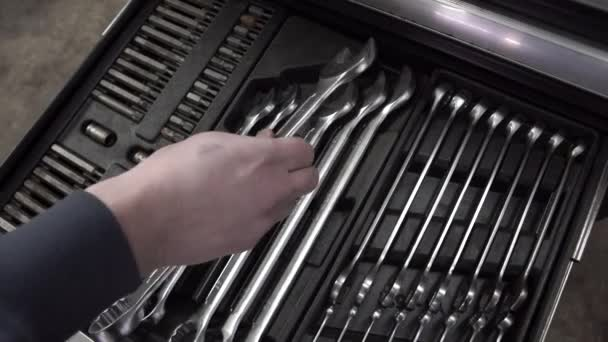 Sada nástrojů pro opravu v autoservis - ruce mechanika, zblízka