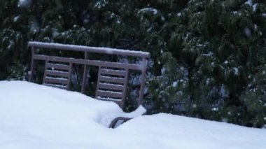 Snowflakes fall over a metallic bench in the park. Slow motion with big snowflakes. Great snowfall over the seats installed on the home yard.