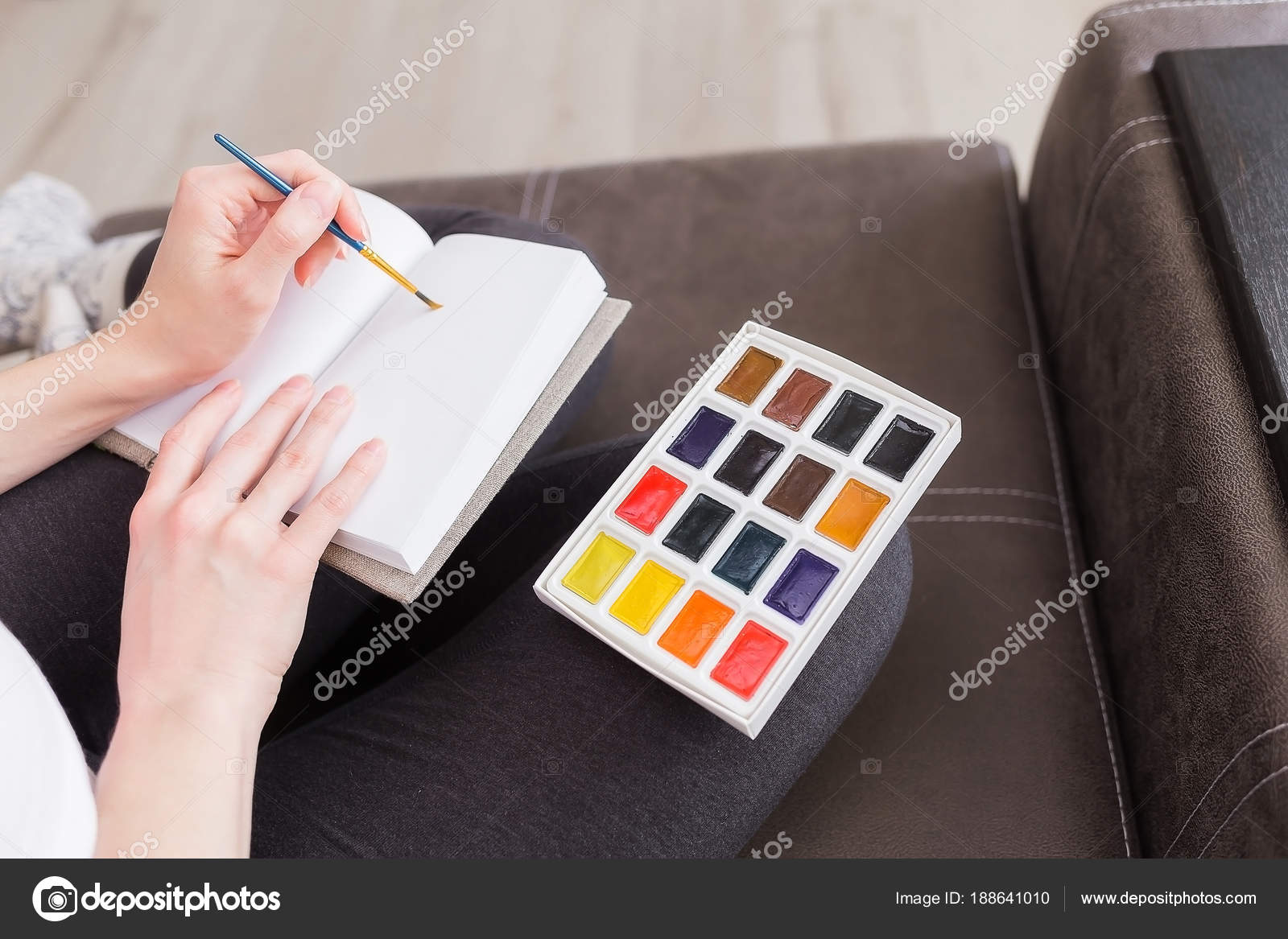 A Girl Holding A Brush In Her Hands And Drawing In A