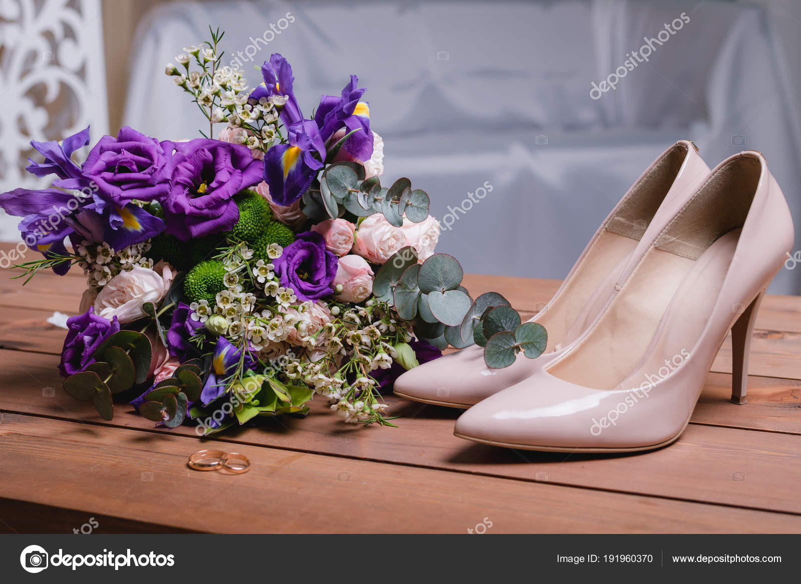 On A Wooden Table A Wedding Bouquet With Green Leaves Purple And