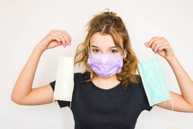 Beautiful teenager brown-eyed girl with brown hair in black t-shirt, wearing lila mask, showing two coloured hygienic masks in hand, looking collection into camera. Mask collection. Mask variety. Quarantine fashion. Horizontal layout. Copy space
