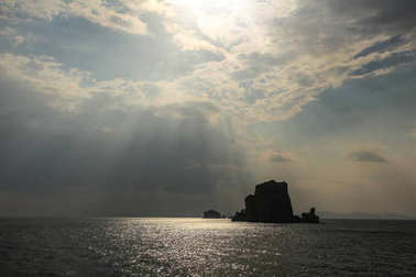 Sun rays shining on small deserted island in Andaman sea