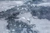 Dettaglio su strato di ghiaccio del fiume completamente ghiacciato, con neve