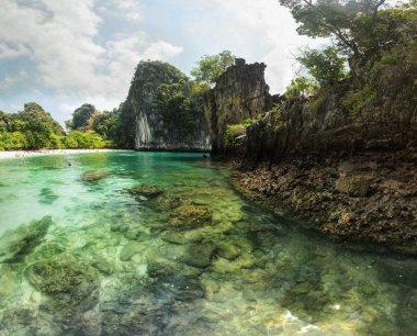 Clear emerald water, rocks visible at sea bottom. Hong Islands b