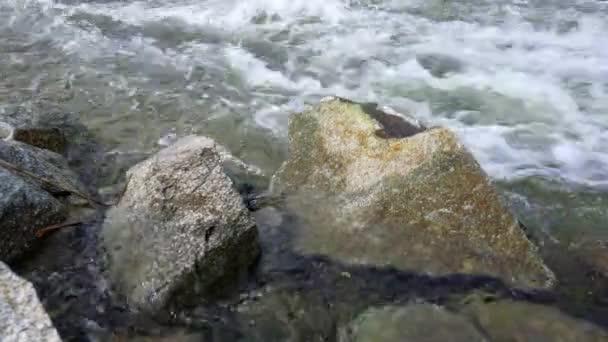 Divoký vodní proud - tekoucí řeka tvořící bílé vlny, velké ostré skály v popředí
