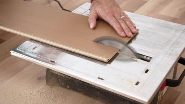 Řezání laminátových podlahových prken na kruhové pilě, detail na mužské ruce držící panel