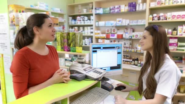 Young female pharmacist serving a customer in a drugstore