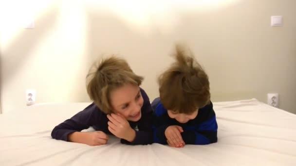 Roztomilý šťastné děti hrají v posteli, rodiče umístěním listu nad nimi