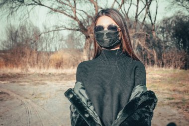 A brunette girl walks down the street in a medical mask, afraid of infection.