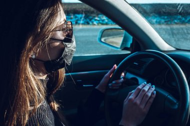 A brunette girl drives a car in a medical mask, fearing infection.