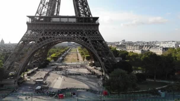 Poblíž Eiffelovy věže kráčí město s davem turistů. Letecký pohled