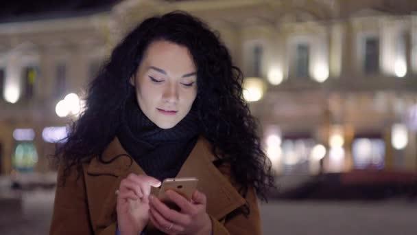 Krásná mladá žena s chytrým telefonem a úsměvem. Píšu zprávu, dívám se na mobil a usmívám se. Použití mobilního telefonu venku v centru města v noci