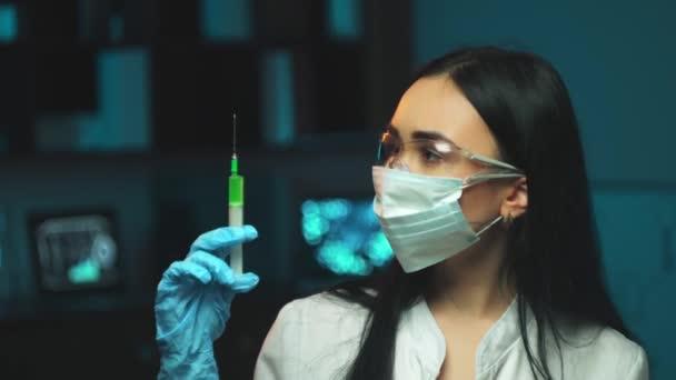 Mladá sestra s lékařskou stříkačkou. Mladá žena lékař nebo zdravotní sestra v chirurgické masce drží injekci v ruce