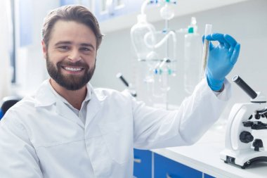 Positive mood. Happy nice successful biologist holding a test tube and smiling while looking at you