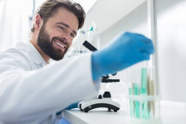 Biological research. Cheerful smart male scientist looking at the test tubes and smiling while working in the bio lab