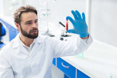 Medical laboratory. Selective focus of blood sample being held by a nice handsome male scientist while sitting in the lab
