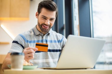 Electronic banking. Positive happy young man holding a credit card and smiling while making an online payment