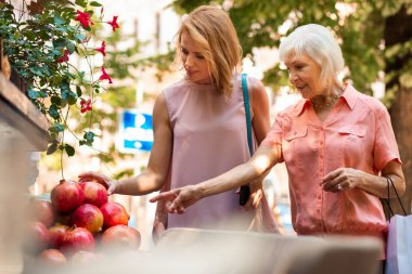Calm aged woman choosing pomegranate with adult daughter outdoors