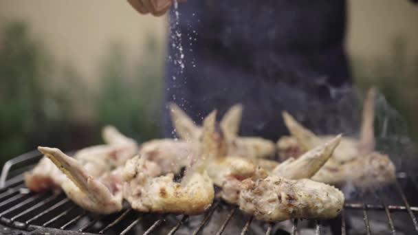 Muž vaření chutné křídla na grilu gril pro venkovní oběd v krásný letní den v domácí zahradě