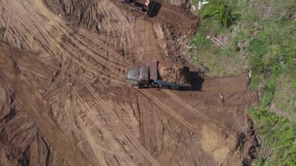Luftaufnahme der Kippladefläche auf einer weiteren Baustelle. In der Nähe Planierraupe Abflachung Oberfläche. 4K.