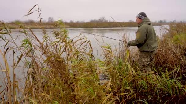 Ősszel horgászik csuka, a halász dob egy kanalat, és forog a forgó tekercs