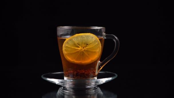 Egy szelet citrom forró teába mártva egy pohár teáscsészében lebeg a felszínre.