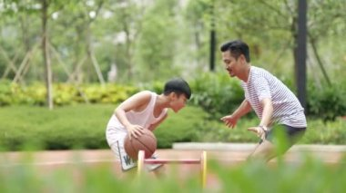 Asian father and son playing basketball in garden in the morning in slow motion