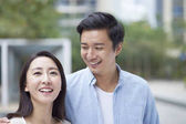 Photo portrait of young Chinese couple standing  smiling outdoor