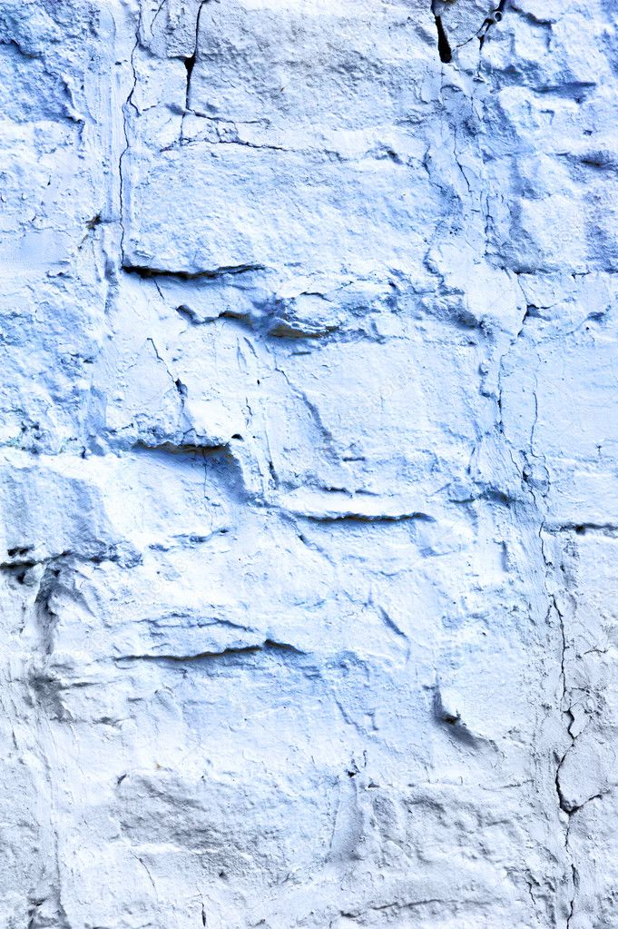 Texture, pattern, background. a wall lined with whitewashed stone with white paint