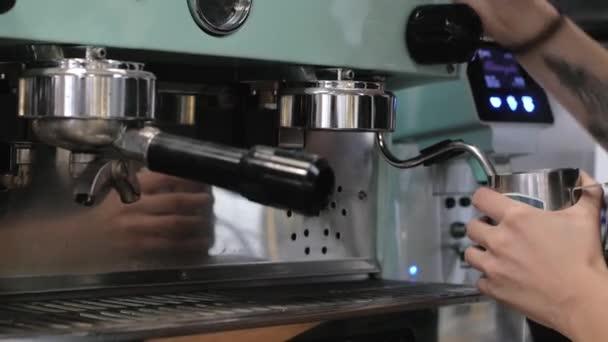 Barista a munkahelyemen. A kávé és kakaó készítésének folyamata. Egy pohár habzó tejet. Elektromos daráló darál kávébab szűrő tartó.