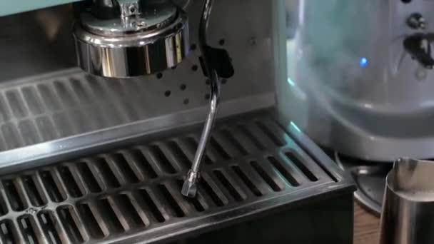 Barista v práci. Proces vaření kávy a kakaa. Sklenici pěnového mléka. Elektrický mlýnek mele kávová zrna v držáku filtru.