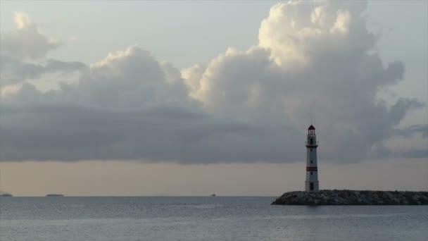 Meereslandschaft bei Sonnenuntergang. Leuchtturm an der Küste. Küstenstadt mit Turgutreis und spektakulären Sonnenuntergängen