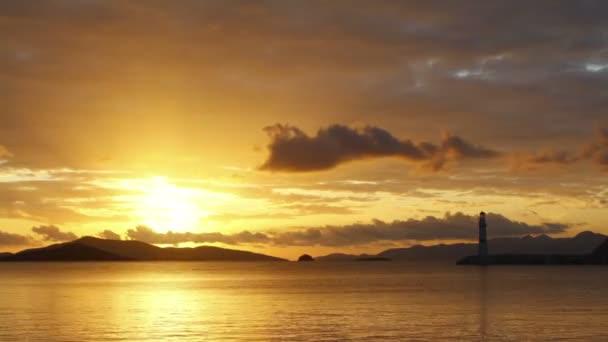 Seascape při západu slunce. Maják na pobřeží. Pobřežní město Turgutreis a velkolepé západy slunce
