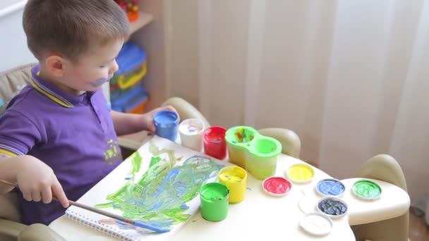 Krásné dítě kreslí s barevnými laky zatímco sedí u stolu