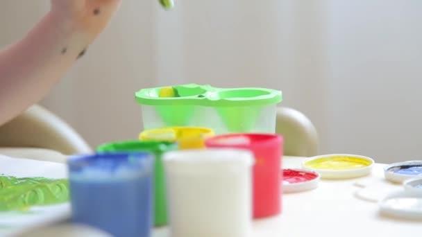 Chlapec ve školce maluje štětcem s barevnými laky